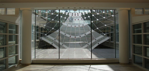 View of the transparent solar clock/calendar from the entry lobby. The solar clock/calendar at Johnson Hall of Science measures hours, days and months via the daily traversing point of sunlight. The 'outdoor room' beyond is formed by the parallel lab wings and two-story glass bridge.