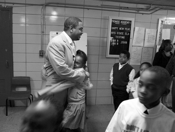Dennis McKesey, the principle of Promise Academy 1 Elementary School, encourages a student with a hug.