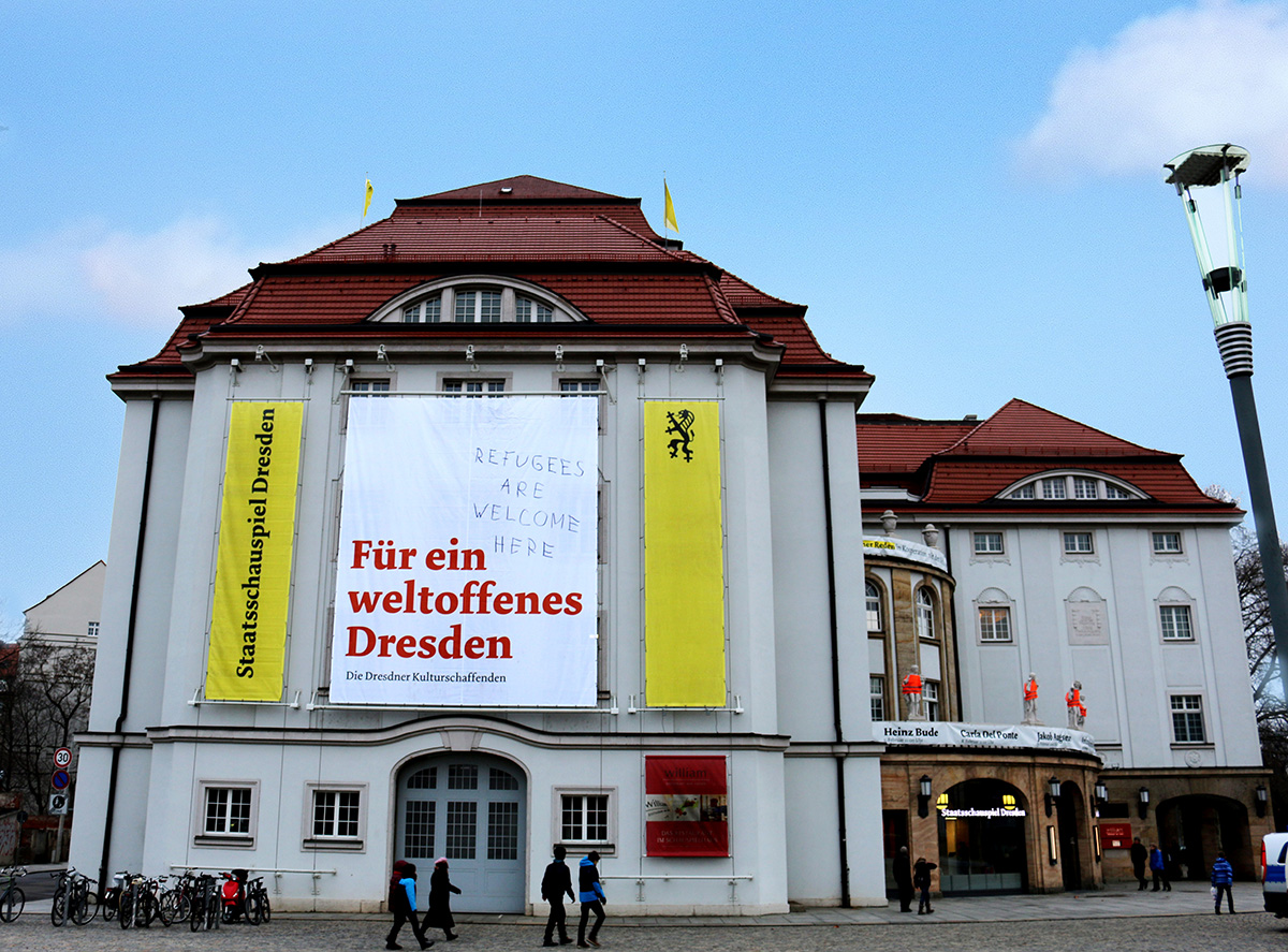 "Frontside of the State Theater Dresden (Staatsschauspiel Dresden) Banner reads ""We support a cosmopolitan Dresden"" (""Für ein weltoffenes Dresden"") with the additional comment ""Refugees are welcome here"" Photo by: Birgit Bräuer © Staatsschauspiel Dresden."
