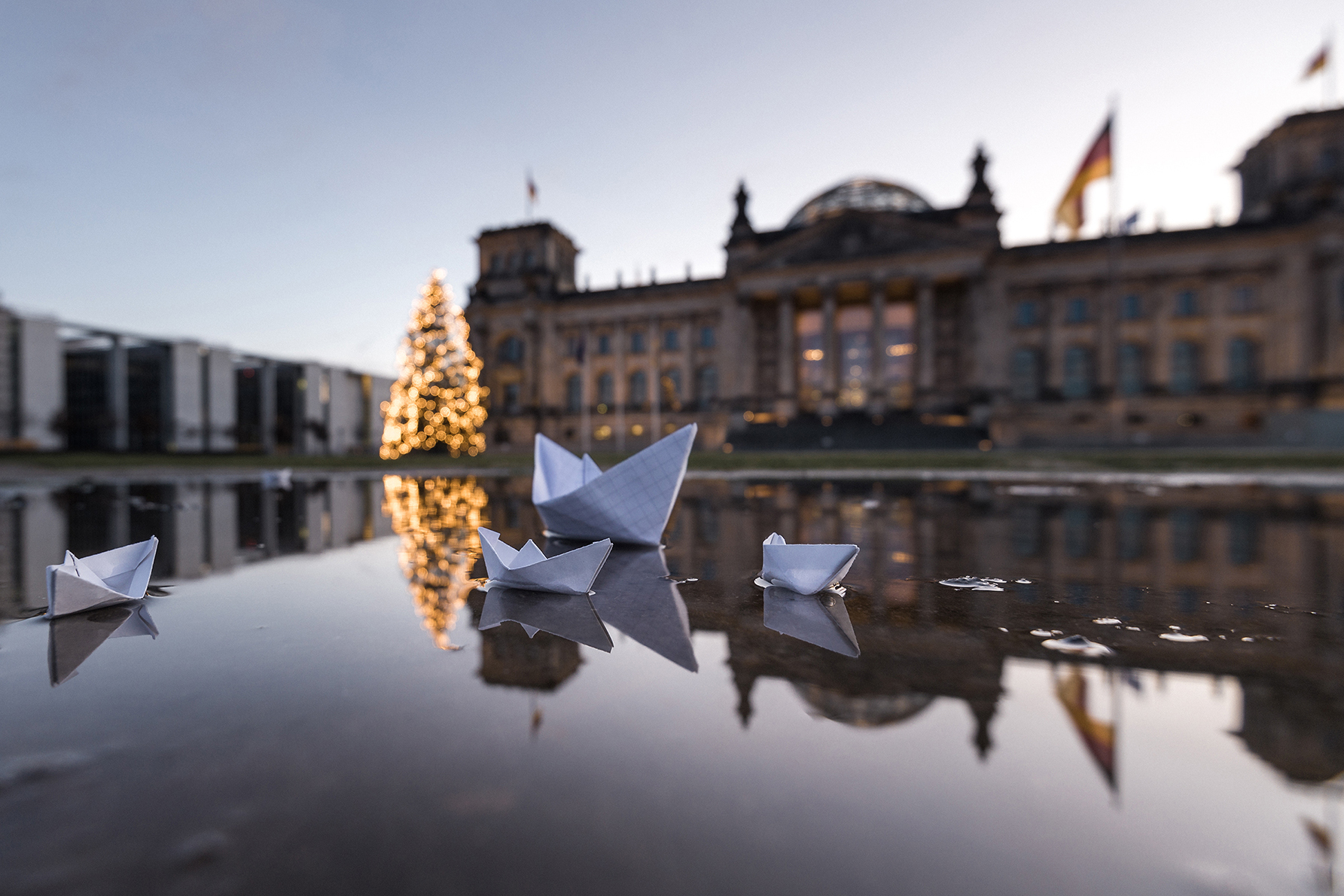 "Delicate origami boats float in a puddle across from the Reichstag in Berlin, Germany. An historical monument built to house the Imperial Diet. Today, the meeting place of the Bundestag ""Federal Assembly"", the lower house of Germany's national legislature. December 12, 2015 Photo by Marcello Zerletti retrieved from Flickr.com"